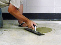 Repairing the cored holes in the concrete slab floor with fresh concrete and cleaning up the Chapin home.