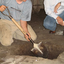 Digging a hole for the engineered fill used in a crawl space support system installation in Greenville