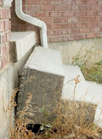 sinking outdoor concrete steps showing cracking and soil washout in Florence