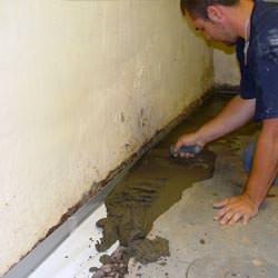 A basement waterproofer installing a perimeter drain system in Florence